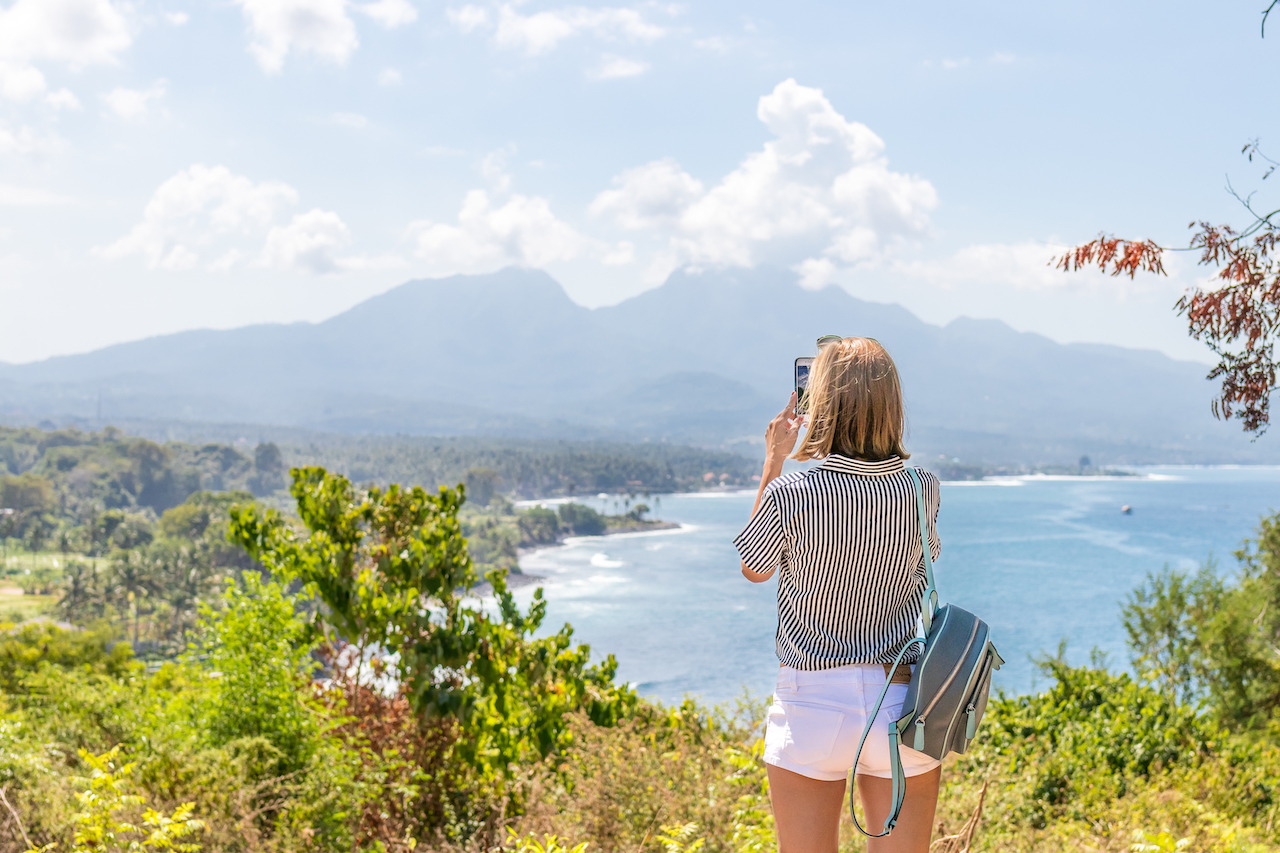 Woman with backpack standing on the cliff of mountain. Bali island.